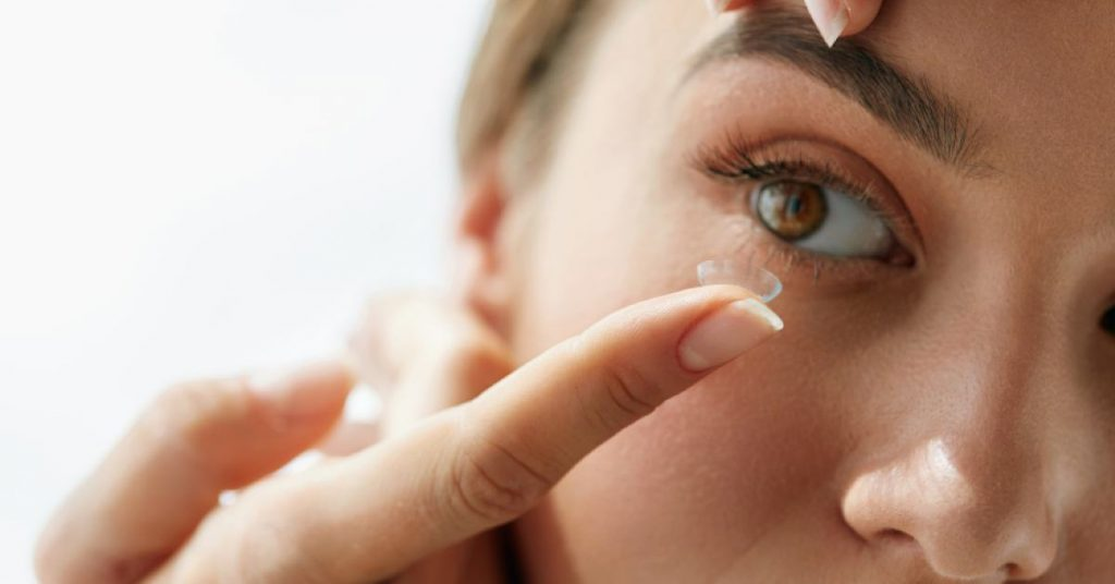 Close up of woman preparing to place a contact lens in her eye