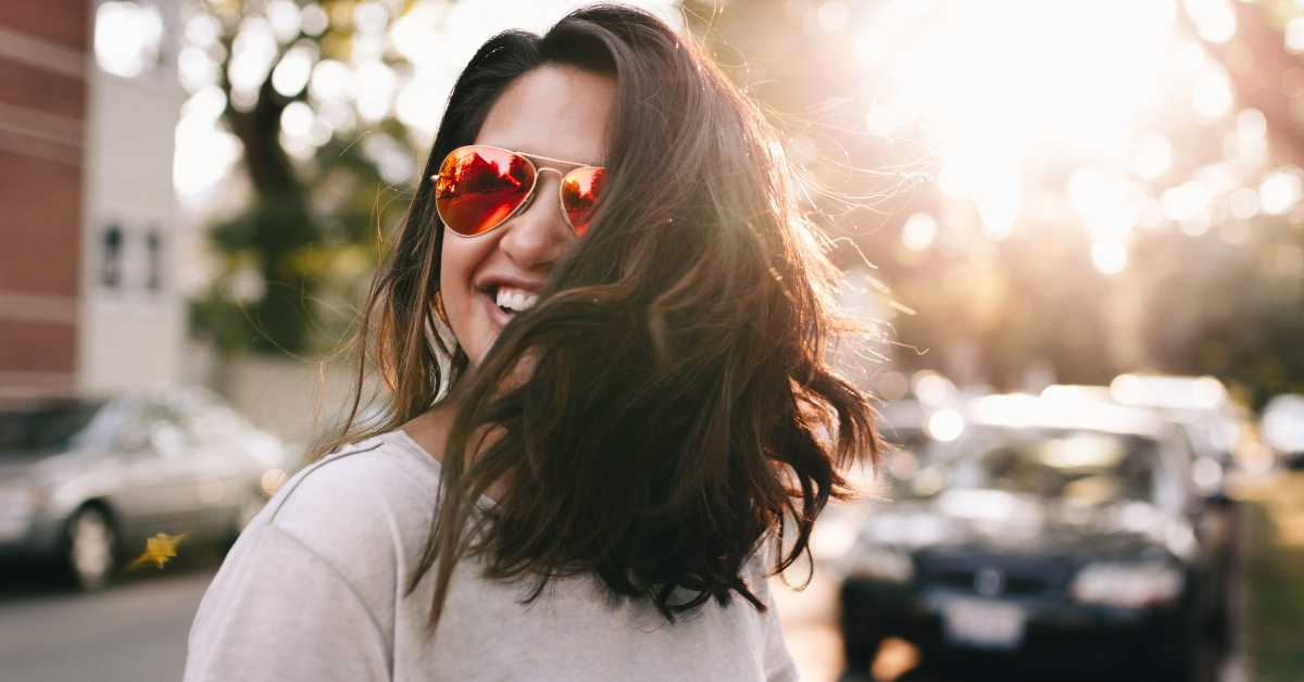 Close up of woman wearing sunglasses standing in the street with the sun beaming behind her