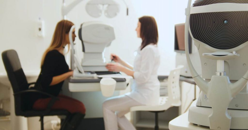 Woman getting her eyes checked by a machine at an optometry appointment