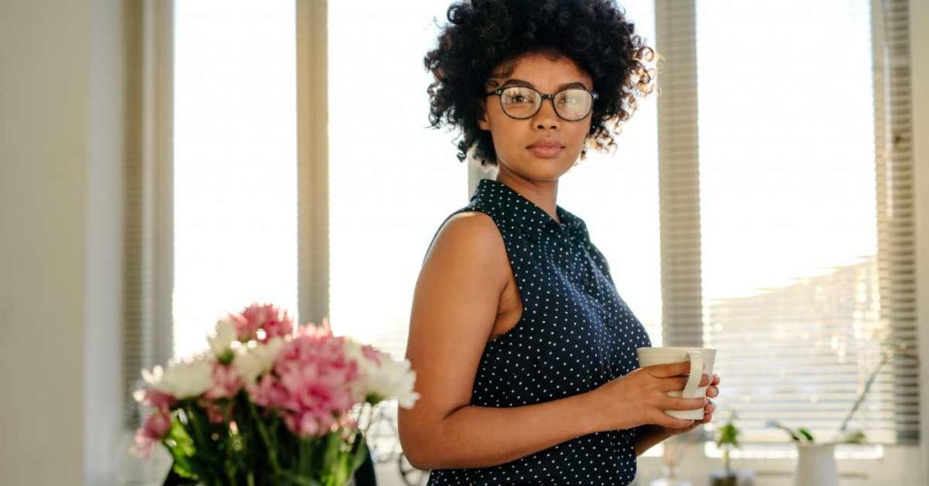 Woman wearing glasses and holding a coffee mug while looking at the camera