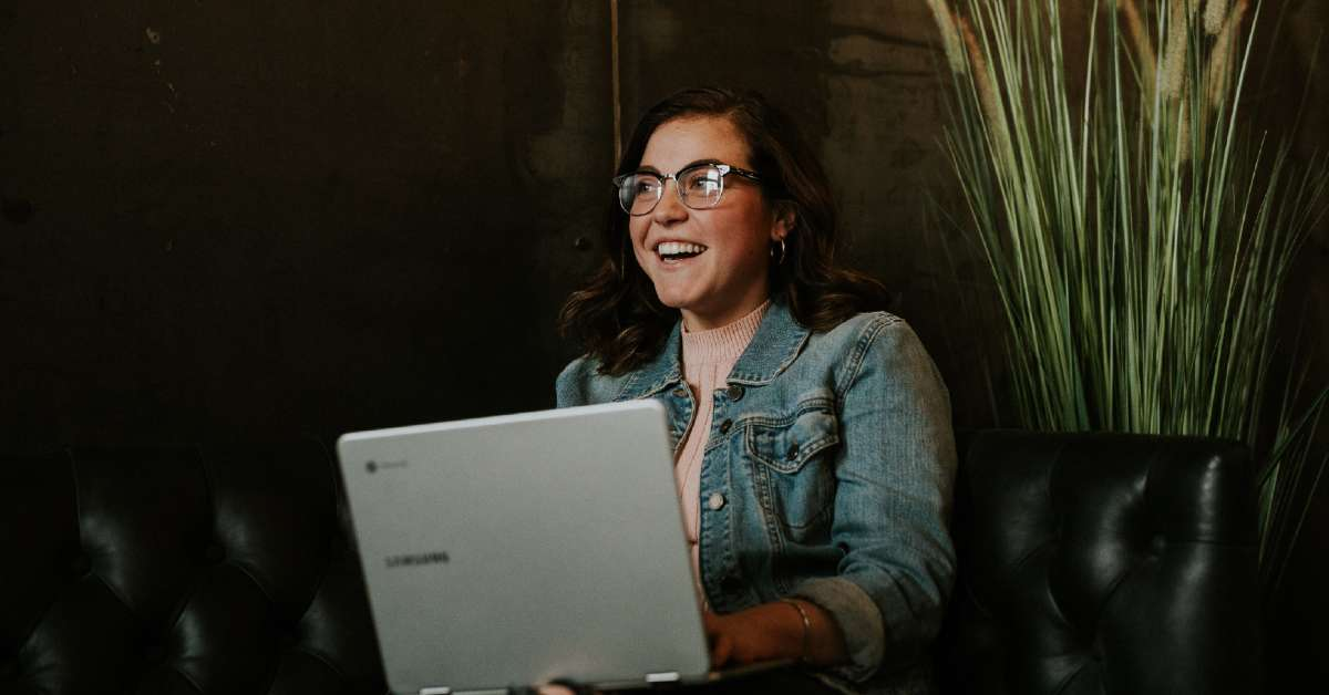 Girl with brown hair and glasses smiling while using a laptop